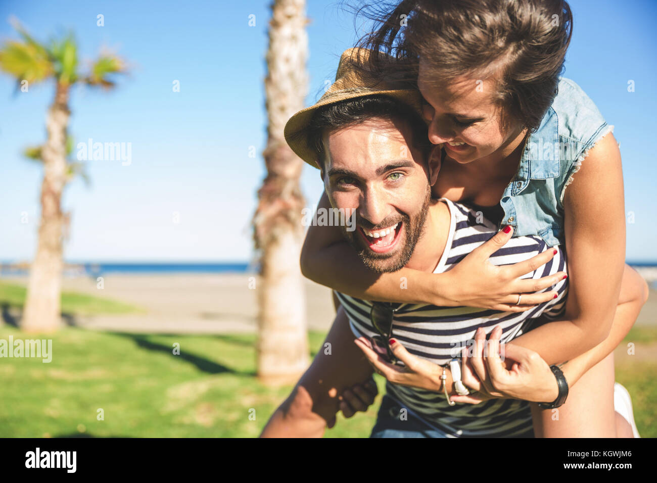 Portrait of happy man giving his girlfriend piggyback ride - Stock Image