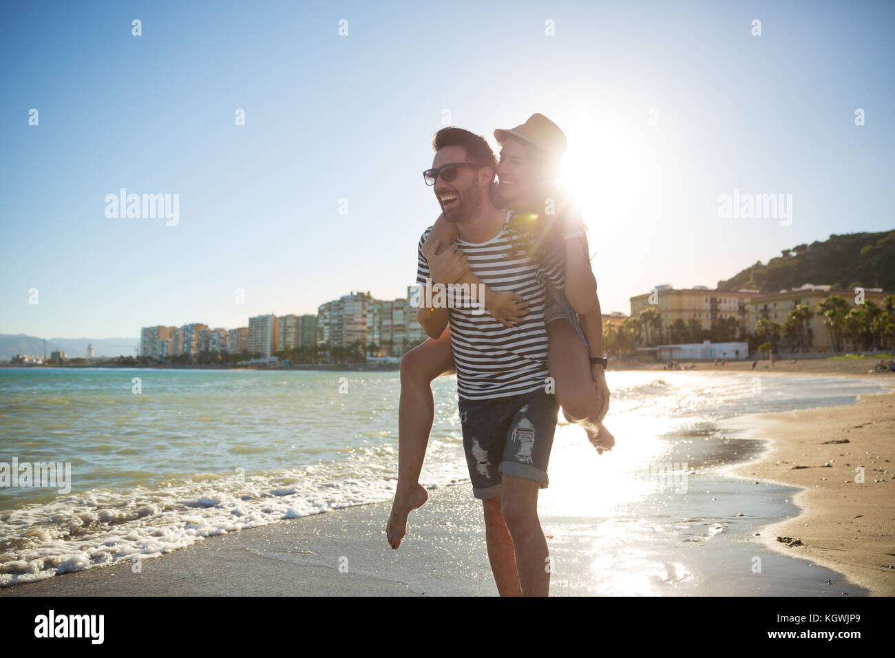 Portrait of happy man giving his girlfriend a piggyback in sunlight on beach - Stock Image