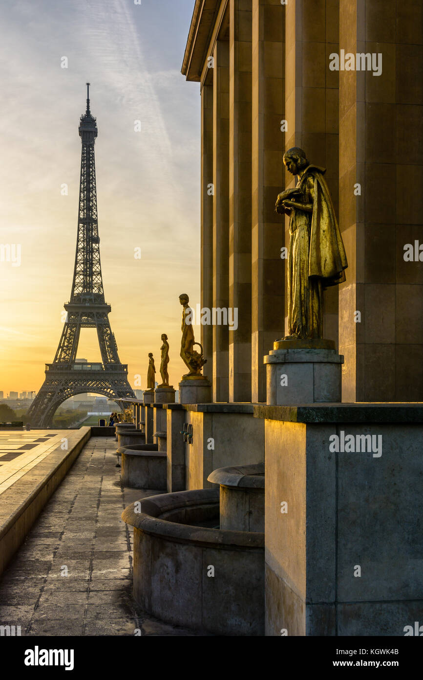 The rising sun illuminates the golden statues on the Trocadero esplanade while the Eiffel Tower stands out against - Stock Image