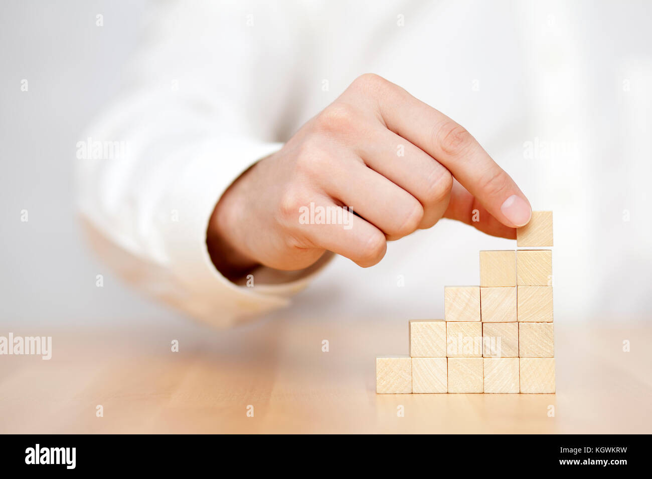Man's hand put wooden blocks in the shape of a staircase. Business success concept. - Stock Image