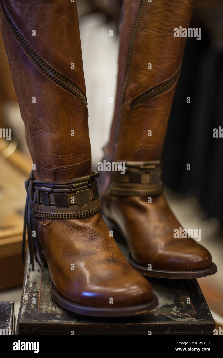 Pair of women's brown leather boots designed in western style displayed on a vintage shoe box Stock Photo