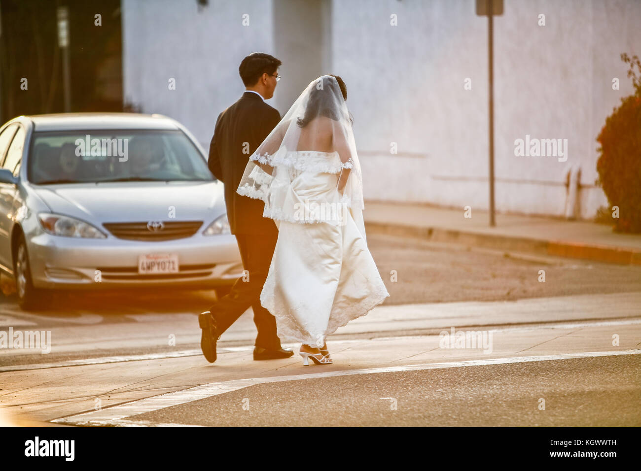 A newly wed couple walks across street and stops traffic - Stock Image