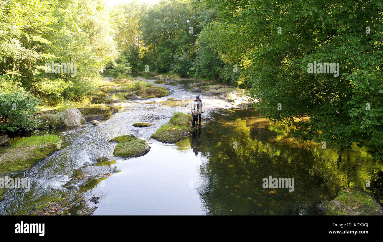 Aerial view of man with kid fly-fishing in river - Stock Image