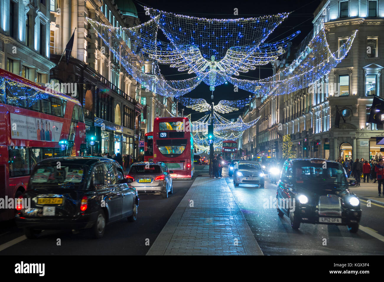 LONDON - NOVEMBER 18, 2016: Red double-decker buses pass under twinkling Christmas angels lighting up the upscale - Stock Image