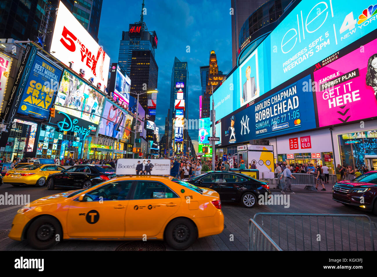 NEW YORK CITY - AUGUST 23, 2017: Bright signage flashes over holiday crowds and traffic zooming past as Times Square - Stock Image