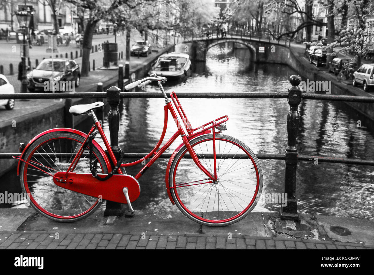 A picture of a lonely red bike on the bridge over the channel in Amsterdam. The background is black and white. Stock Photo
