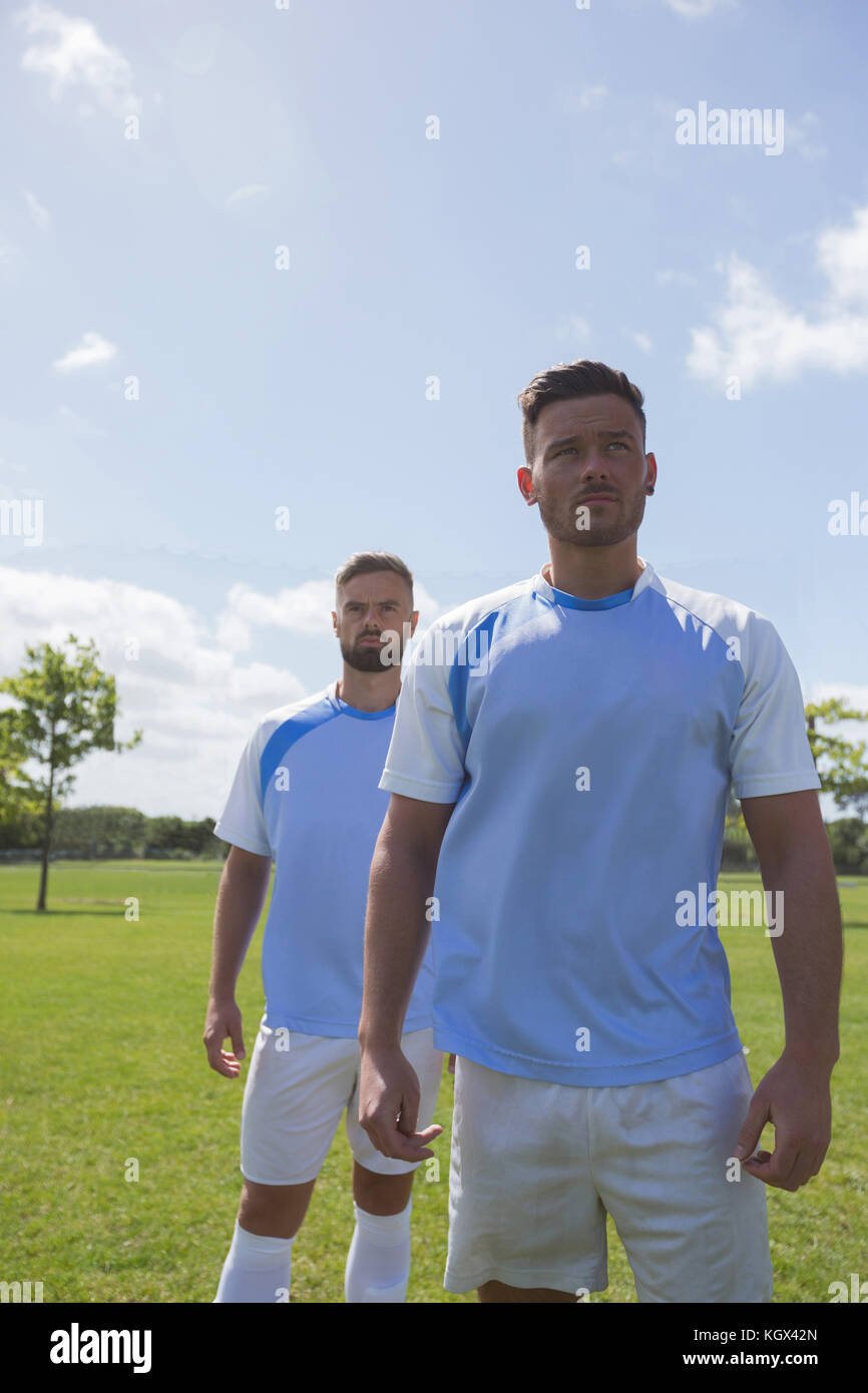 Football players standing in ready position on ground - Stock Image