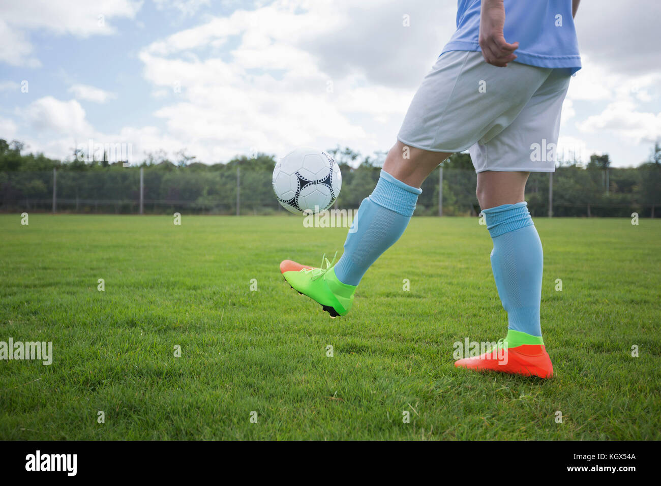 Football player juggling soccer ball in the ground - Stock Image