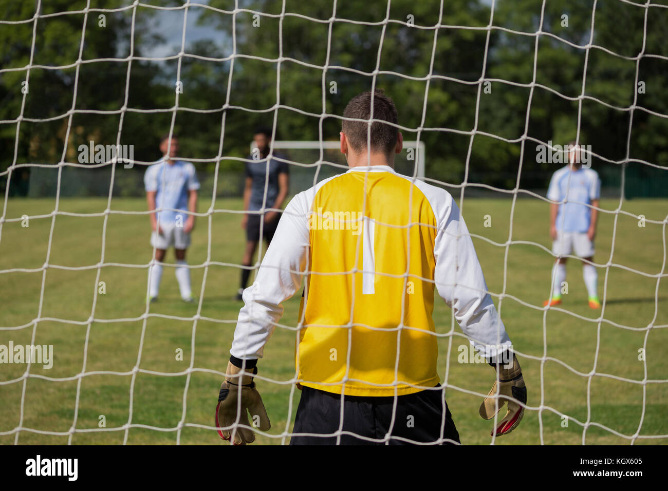 Soccer players ready to kick ball from penalty spot on a sunny day - Stock Image
