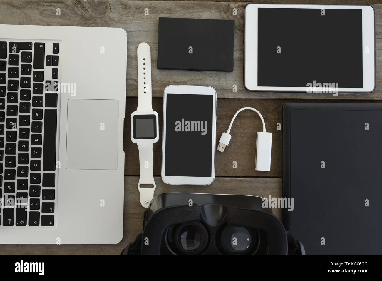 Overhead of various electronic gadgets on wooden surface - Stock Image