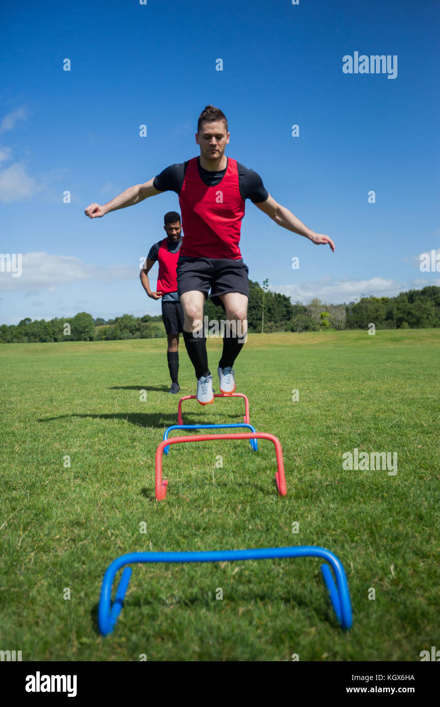 Soccer players practicing on obstacle in ground - Stock Image