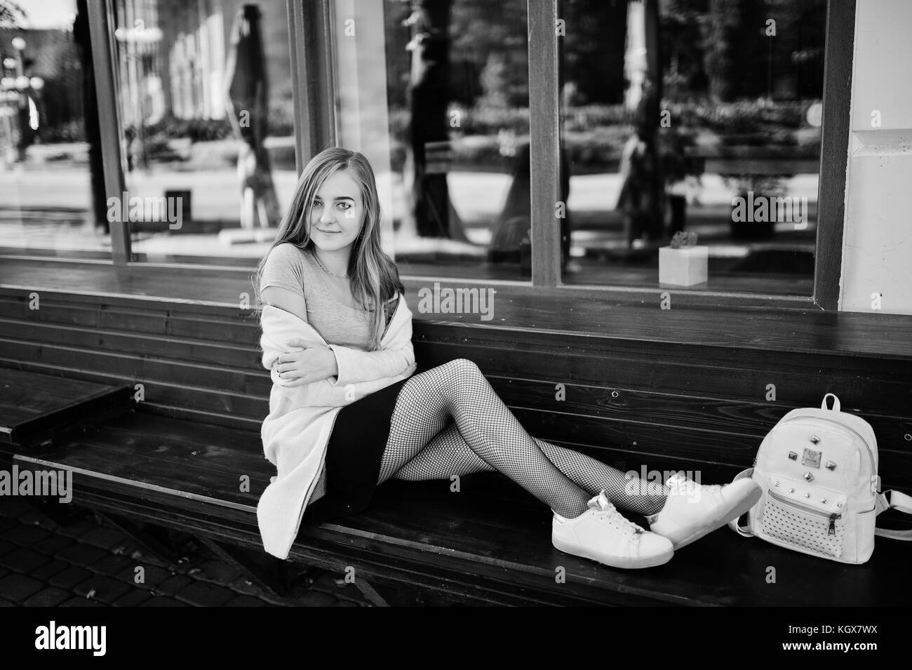Young blonde girl in black skirt and pink coat with woman backpack sitting on bench at
