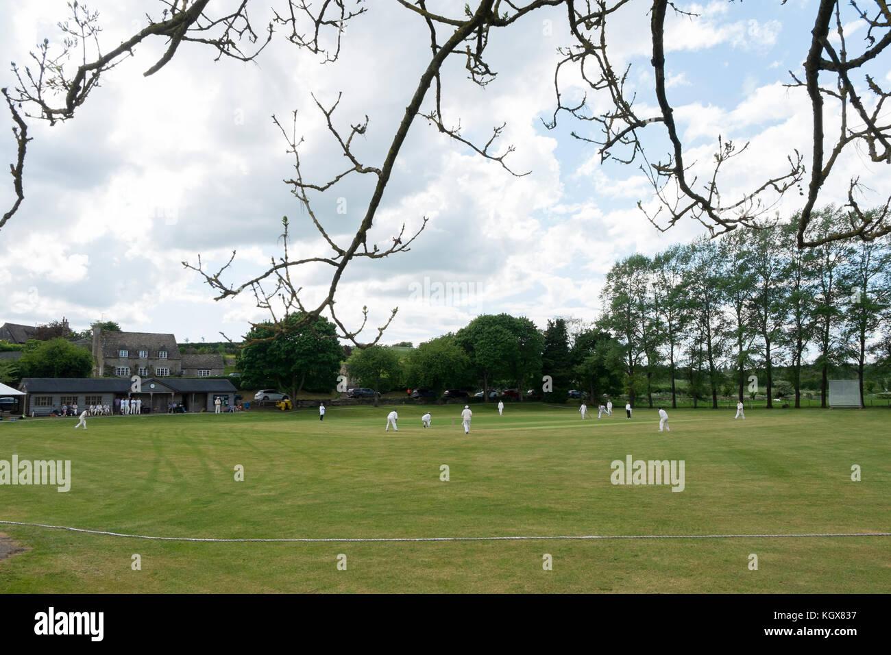Cricket match on the green at Swinbrook, Oxfordshire, UK. Stock Photo
