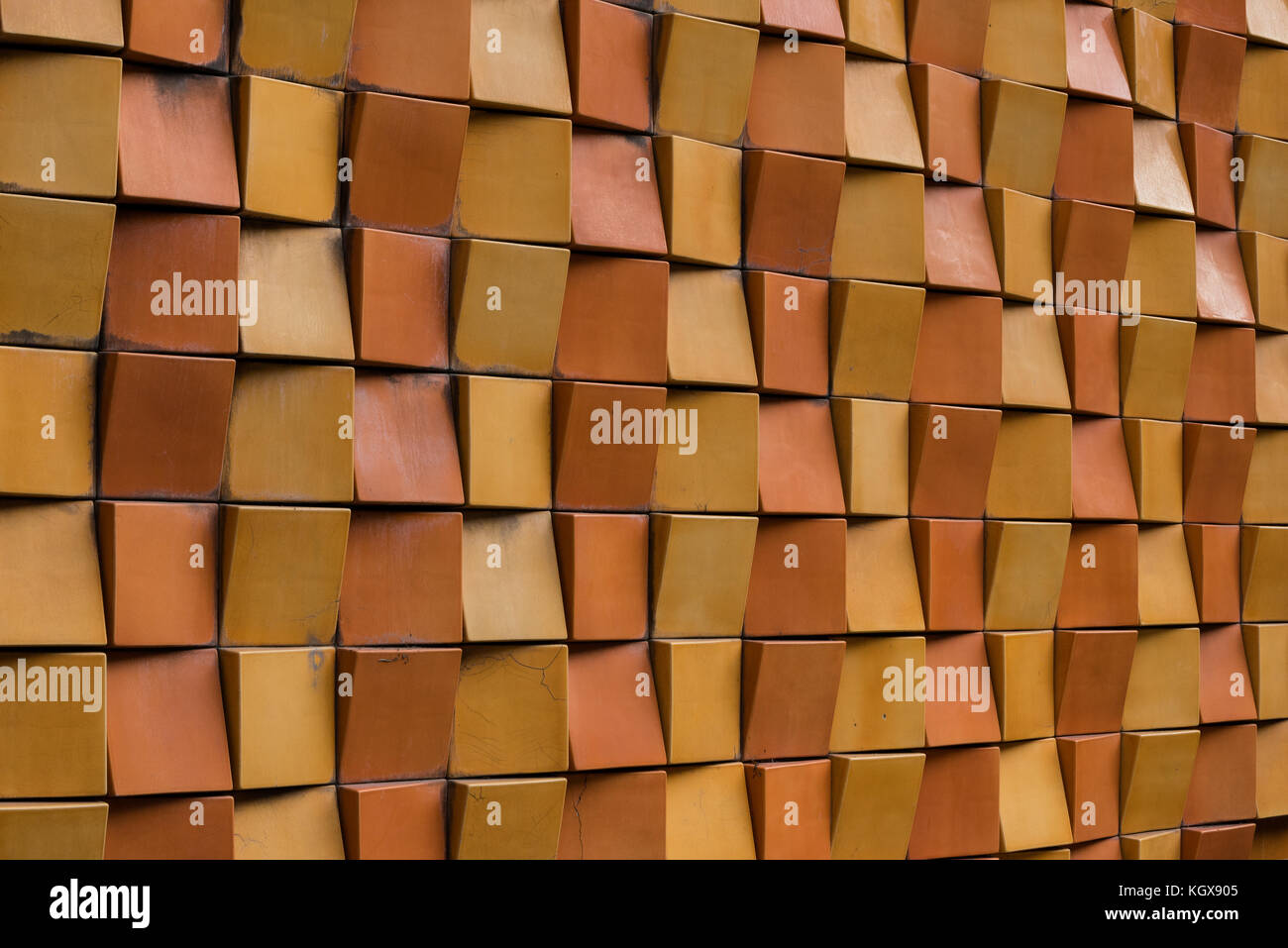 Exterior brick wall in multiple shades of yellow and orange forming decorative pattern in city - Stock Image
