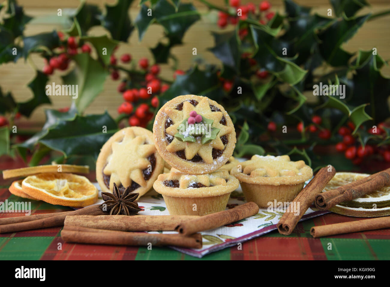 Christmas food photography image with traditional iced pastry fruit mince pies and star top with real fresh green - Stock Image