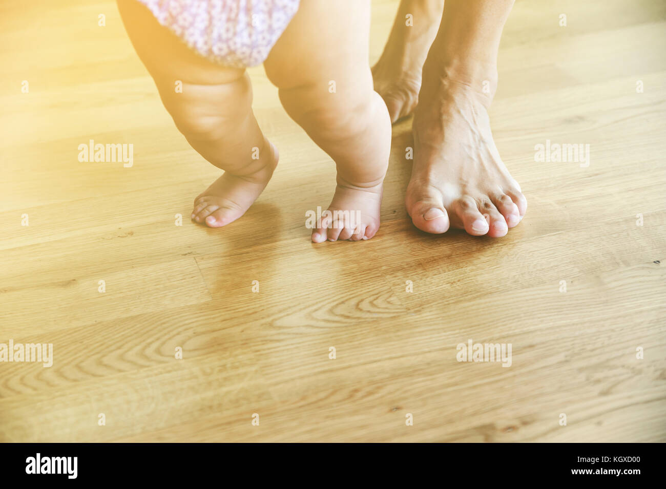 Baby's and mother's feet are walking on the wooden foor. Dream blurry. - Stock Image