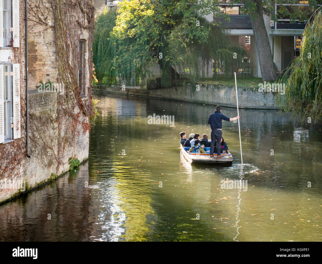 Punting in Cambridge on the river cam UK, A punt chauffeur takes tourists on a river trip - Stock Image