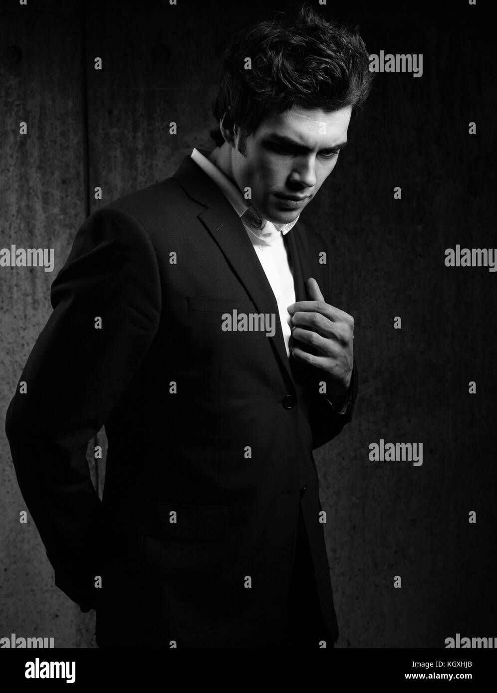 ff92c881 Charismatic handsome male model posing and looking down in fashion suit and white  style shirt on dark shadow background. Closeup portrait. Black and w