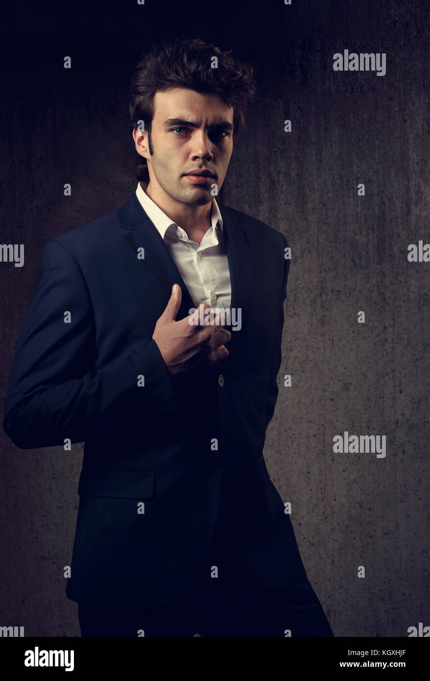 7785561a Charismatic handsome male model posing in fashion suit and white style  shirt looking on dark shadow background