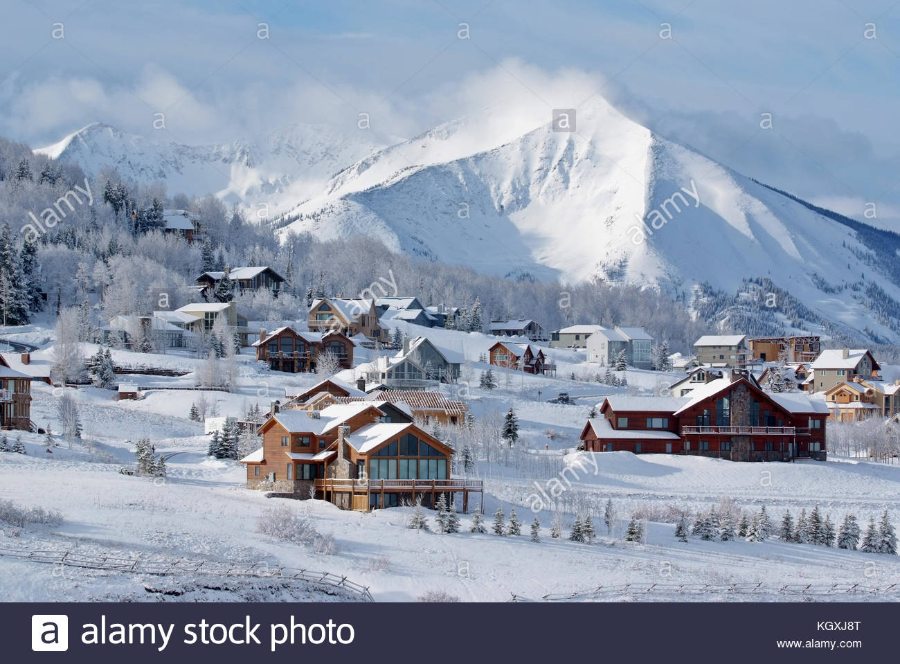 Early morning sun lights homes in Mount Crested Butte, Colorado with Whetstone Mountain in the distance. Stock Photo