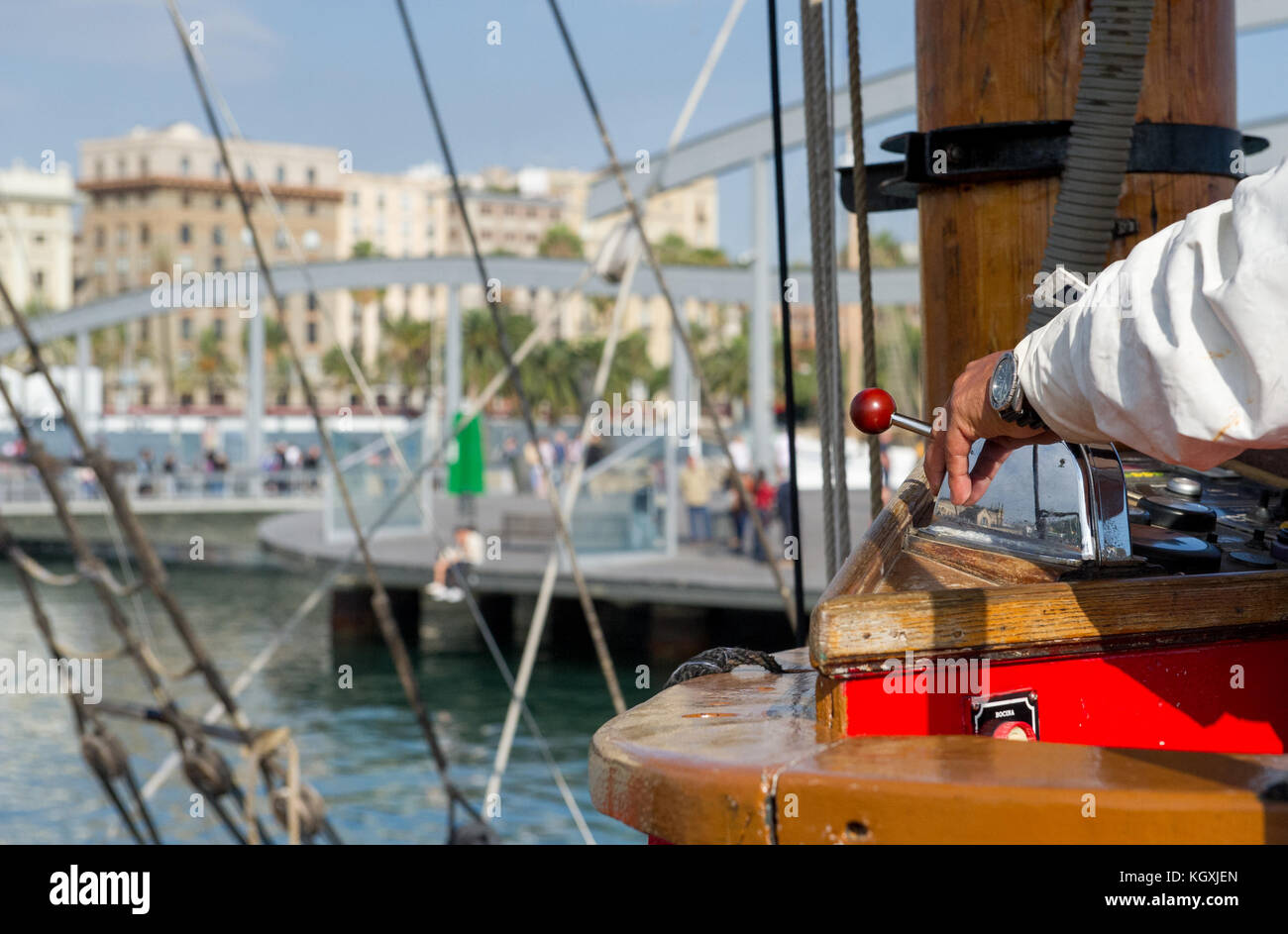 Captain controlling a wooden boat into the harbour at Port Vell, Barcelona. - Stock Image