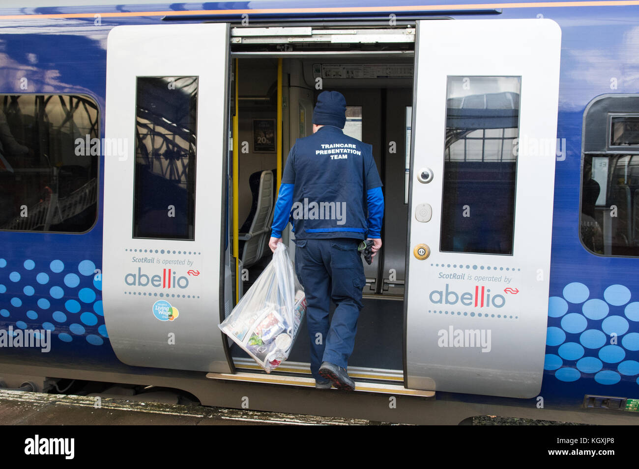 ScotRail train cleaner - traincare presentation team - entering train to clean it as it terminates at Ayr train - Stock Image
