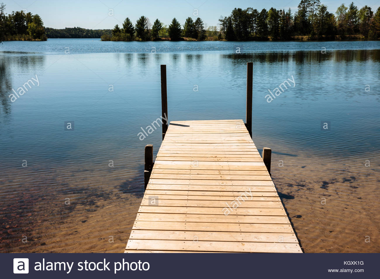 The pier invites one to jump off the end into Star Lake, near Star Lake, Wisconsin in Vilas County in late May - Stock Image