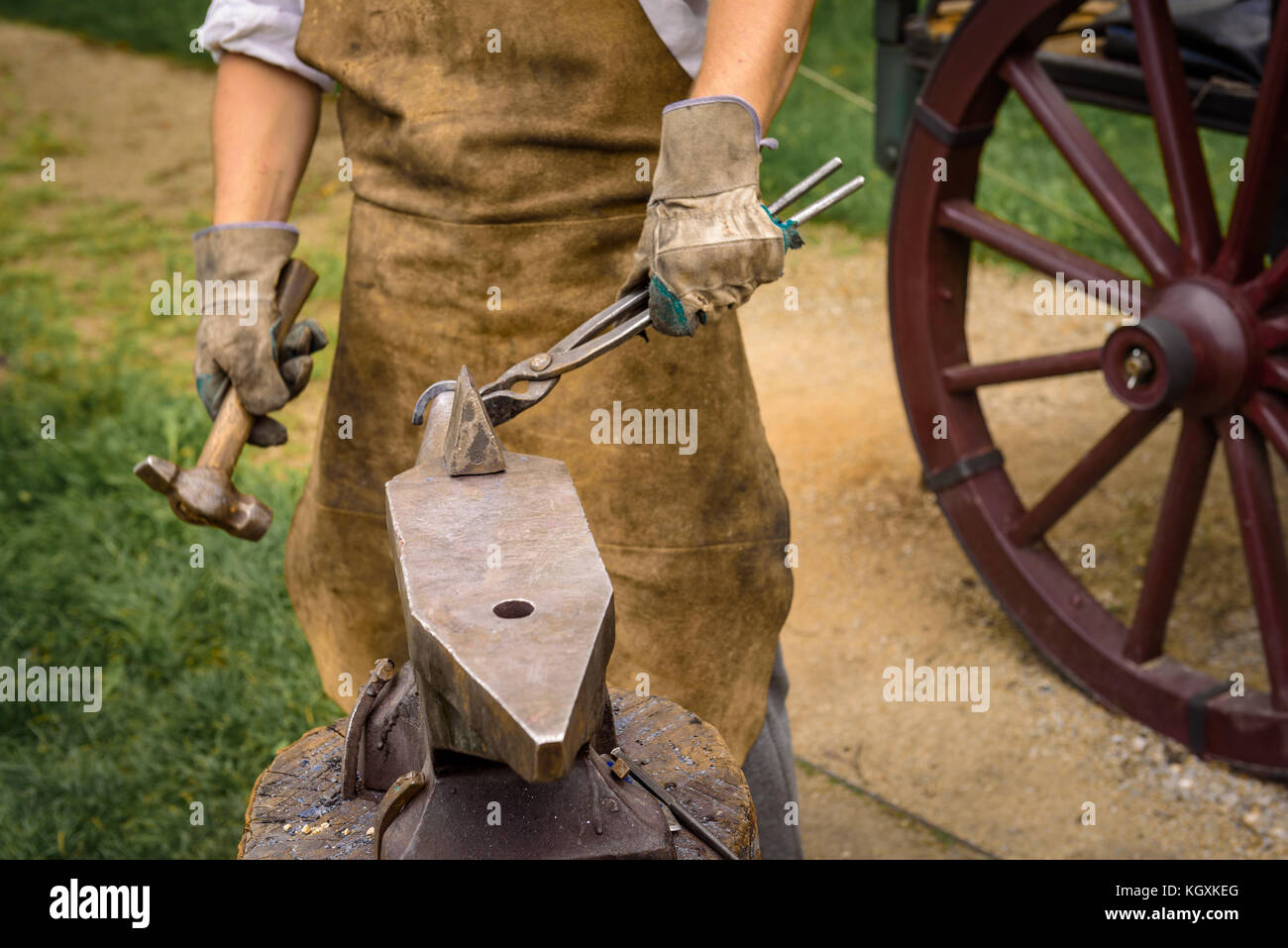 Blacksmith working on an iron object with a hammer during a workshop. - Stock Image