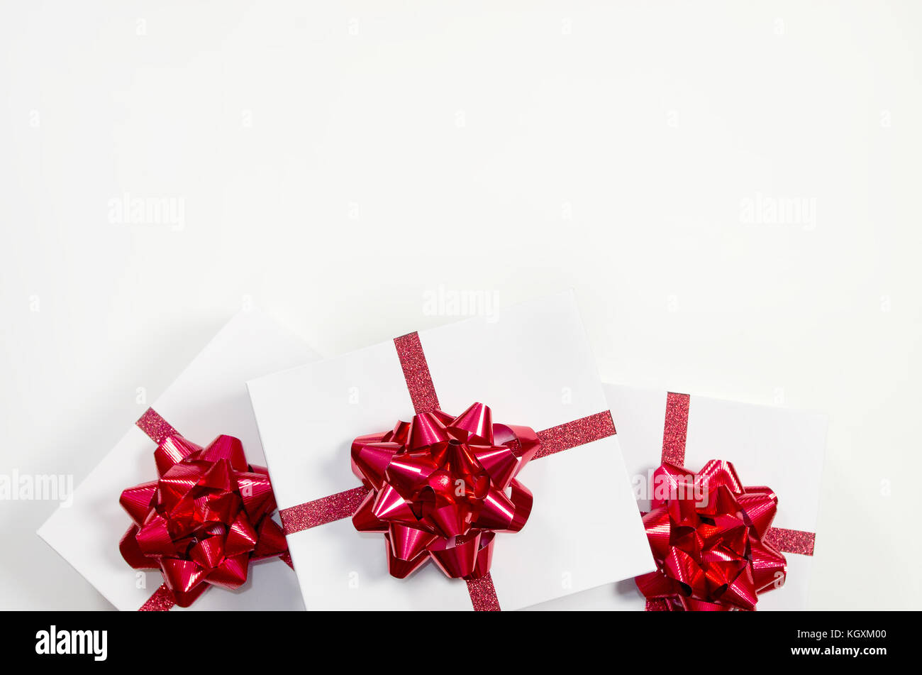 Three Christmas presents with red bows on a white background - Stock Image