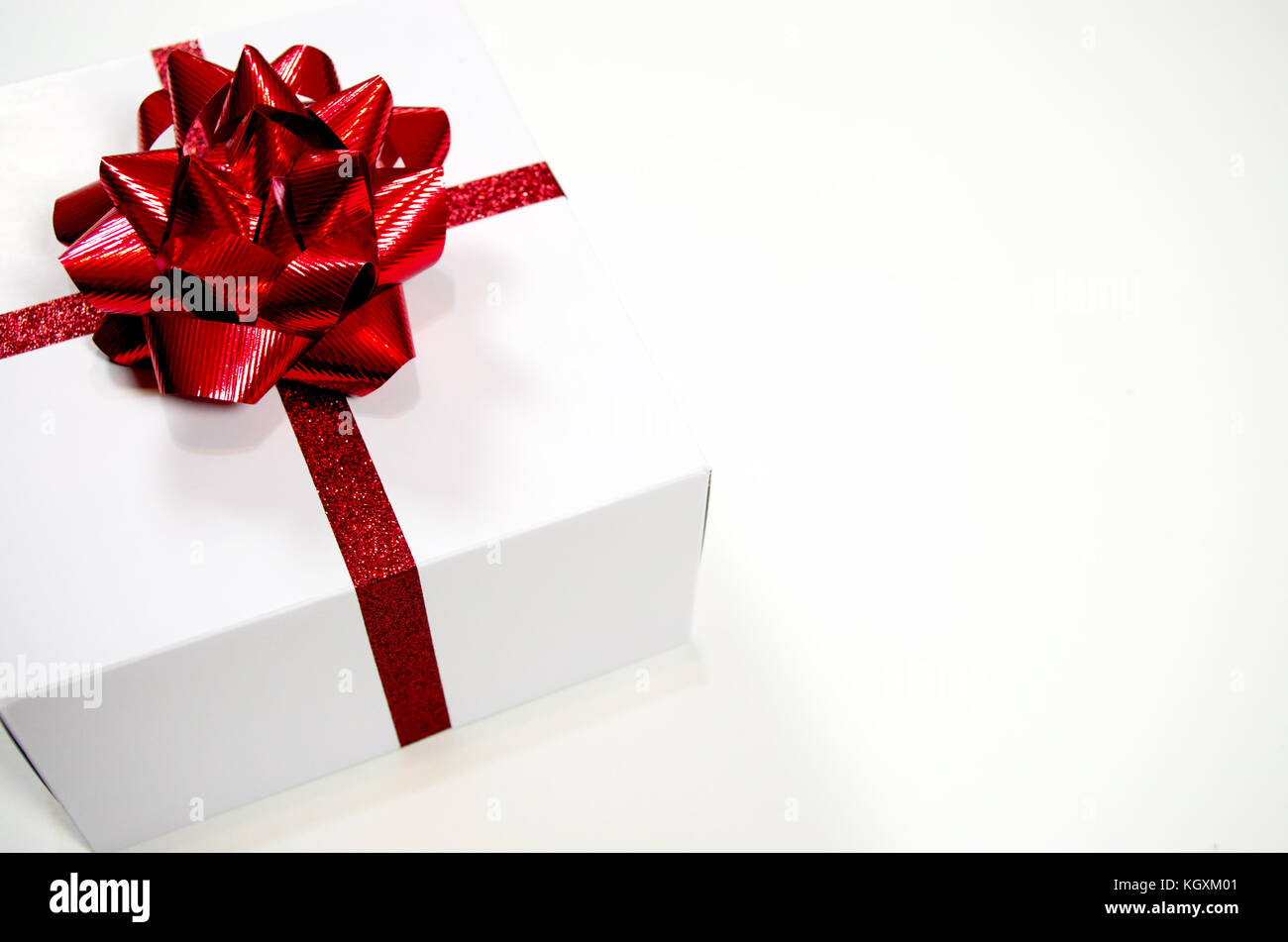 Single Christmas present with red bow on a white background - Stock Image