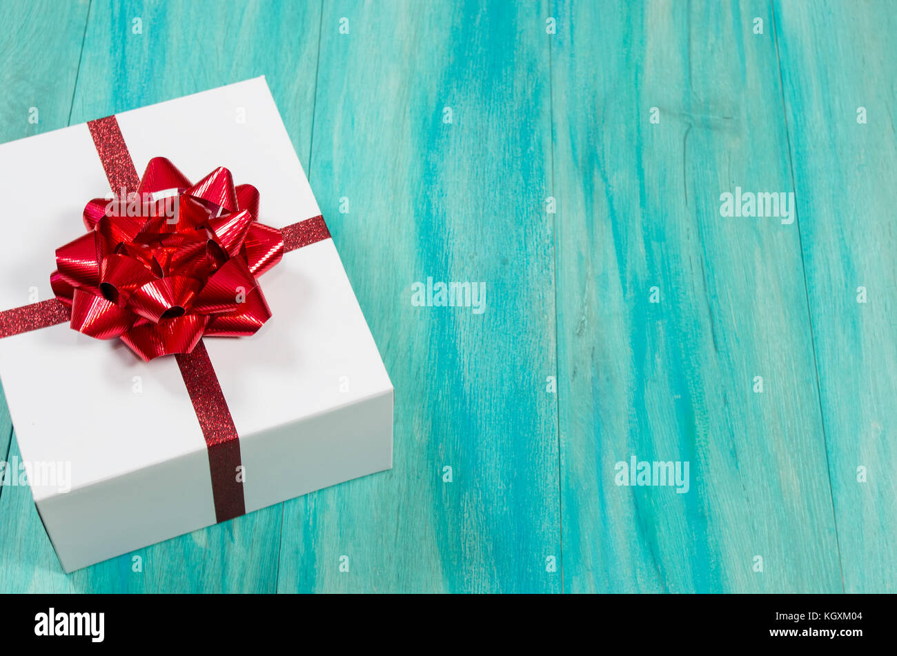 Offset Single Christmas present with red bow on a distressed teal wood background - Stock Image