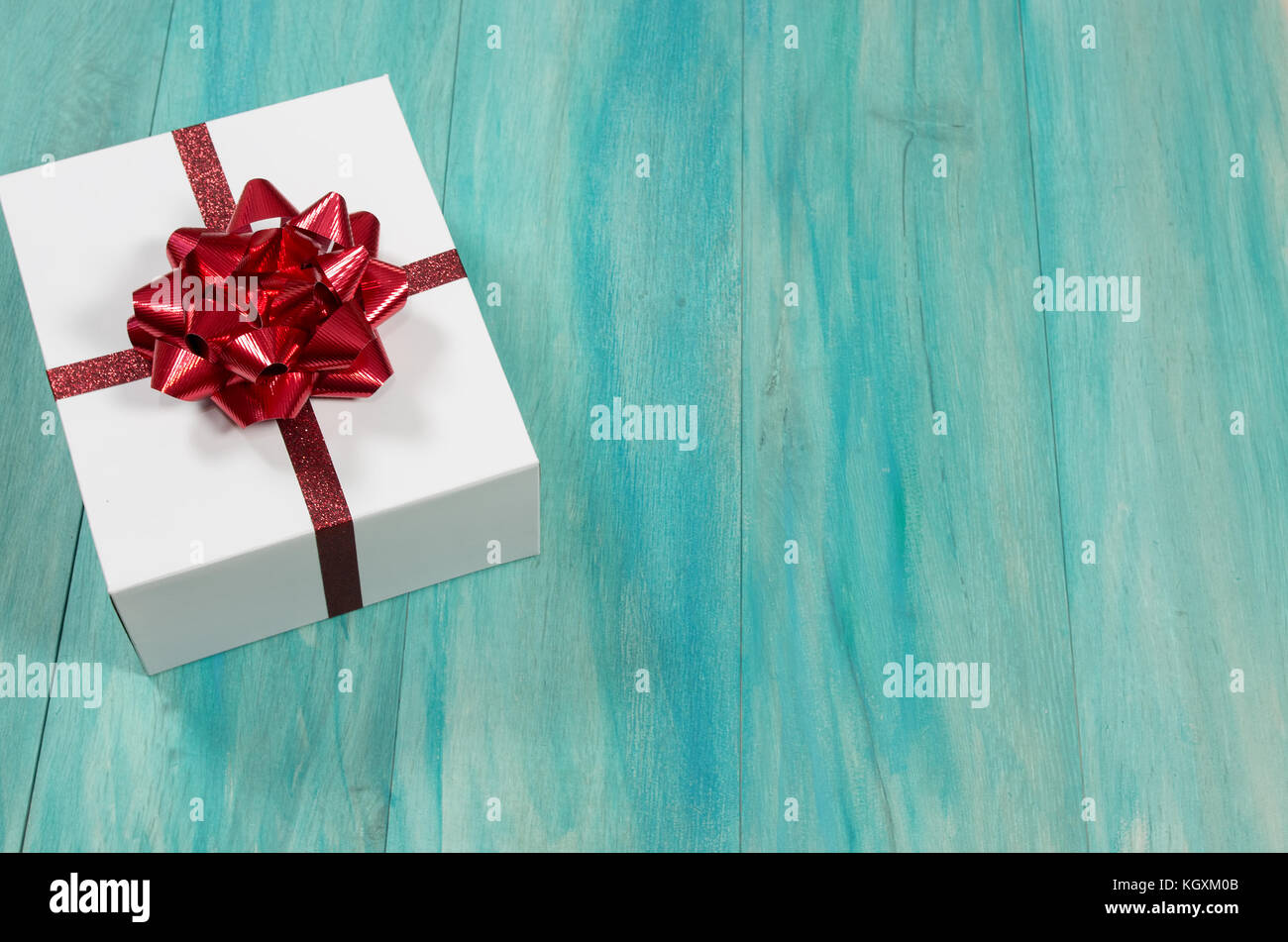 Single Christmas present with red bow on a distressed teal wood background - Stock Image