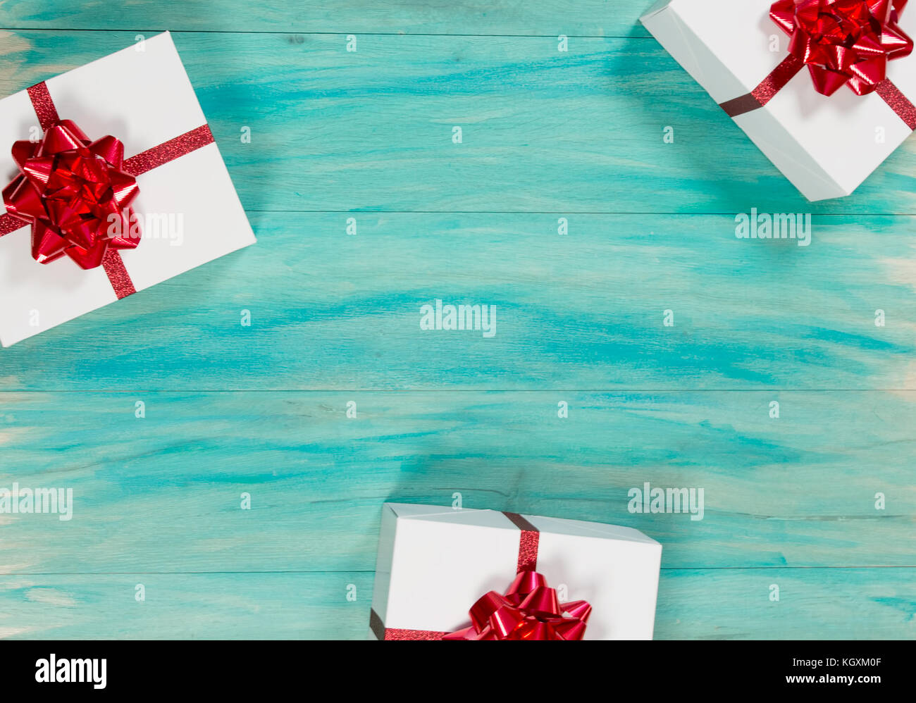 Christmas presents with red bows  on a distressed teal wood background - Stock Image