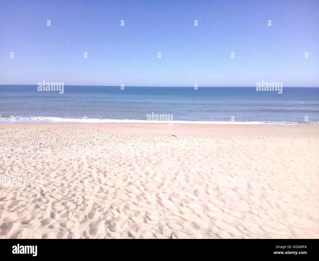 empty beach view with flat ocean on blue sky - Stock Image