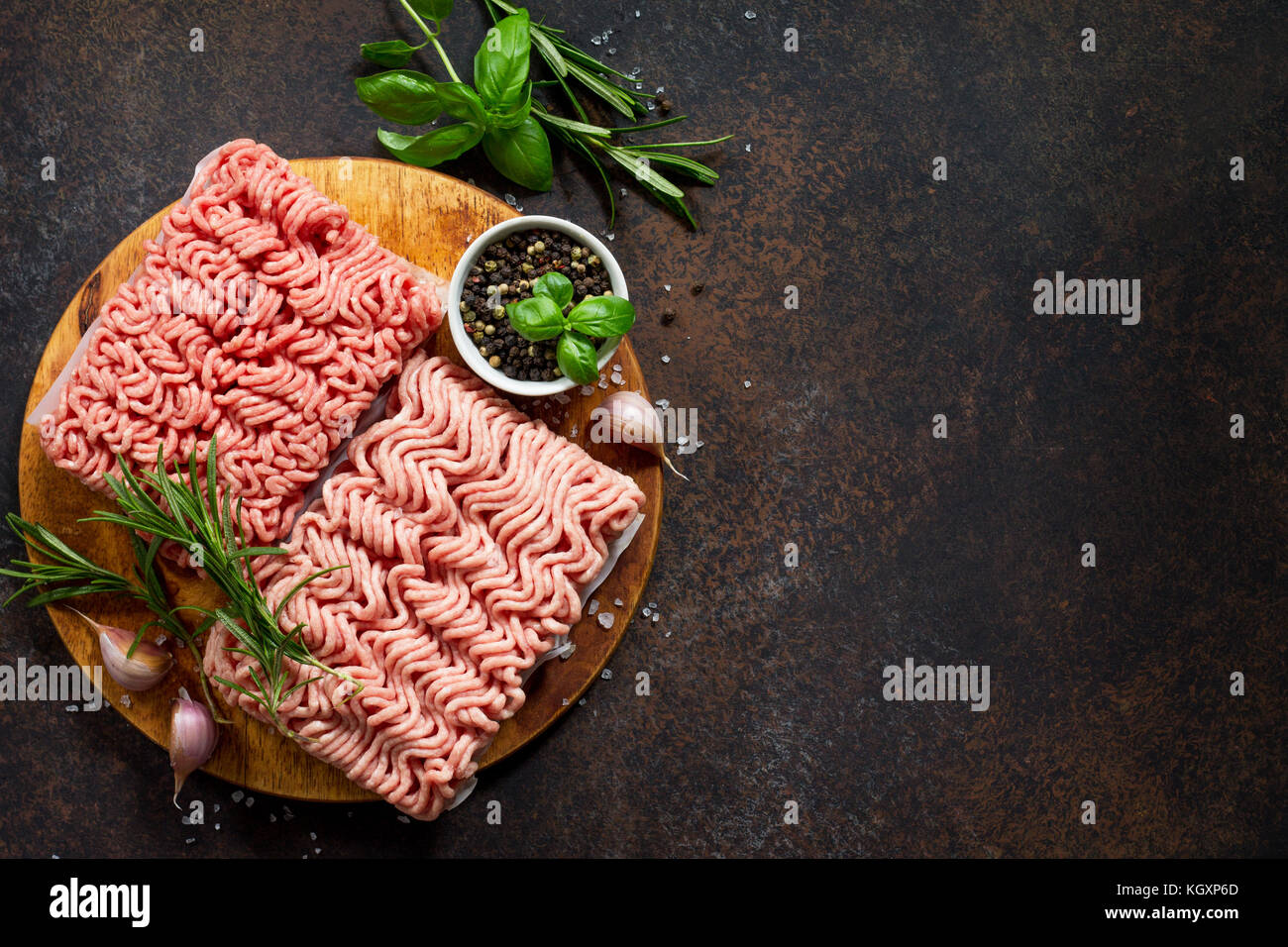 Assorted minced pork and beef with fresh leaves of rosemary and basil. Copy space. - Stock Image