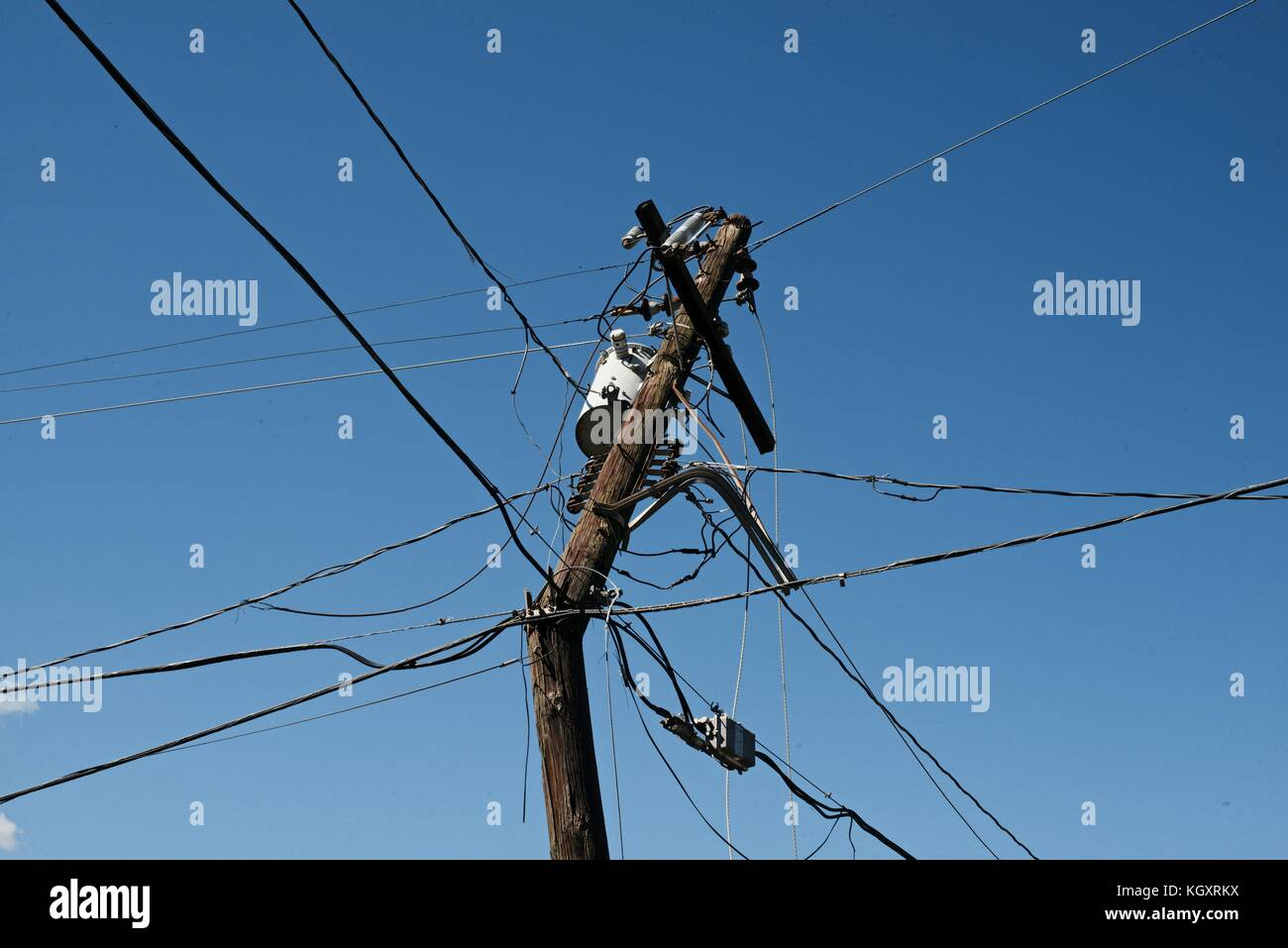 A damaged and unstable power line hangs in the air during relief efforts in the aftermath of Hurricane Maria November Stock Photo