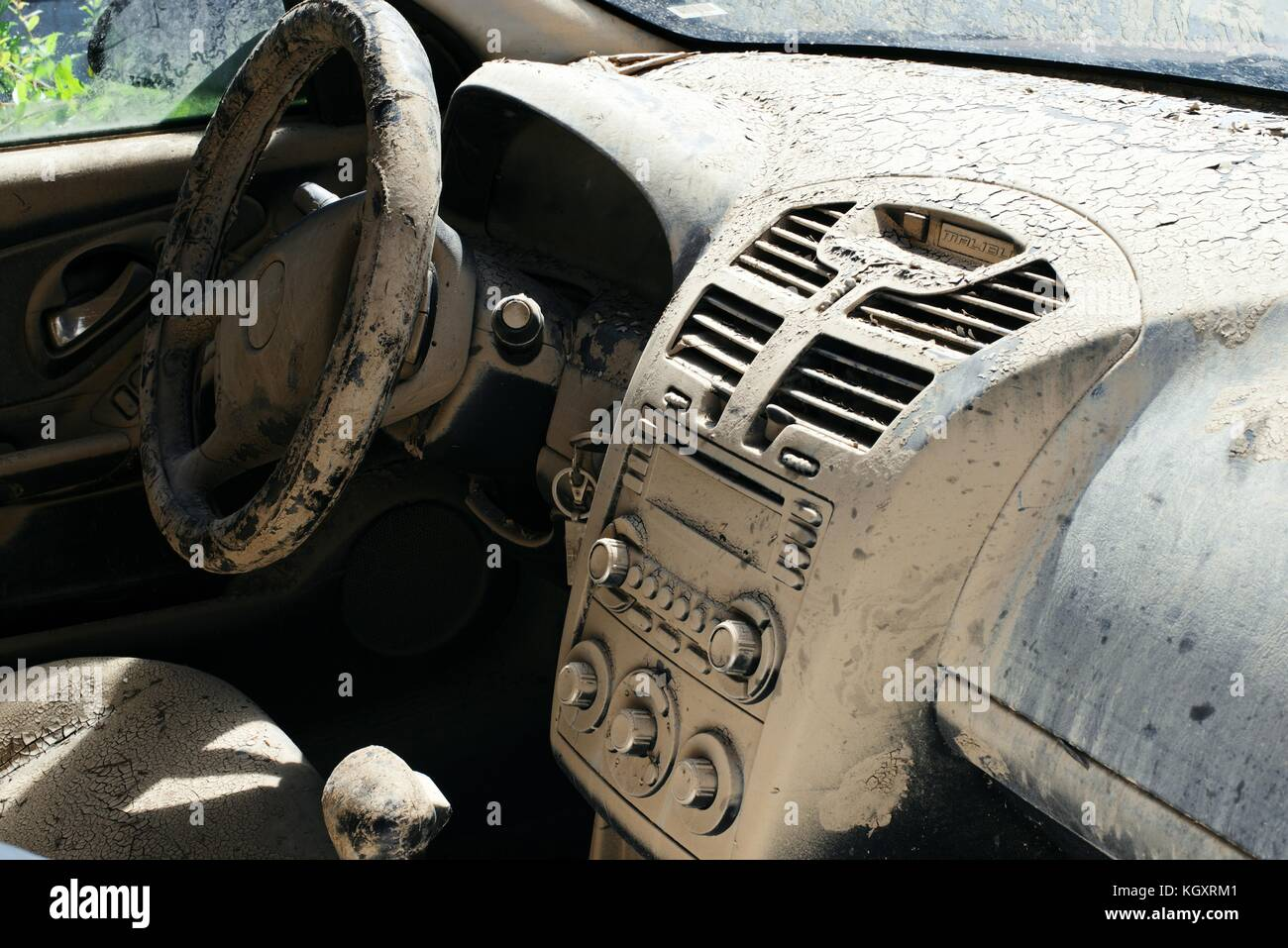 Dirt and mud cakes a damaged car after the flooding caused by Hurricane Maria November 1, 2017 in Toa Baja, Puerto Stock Photo
