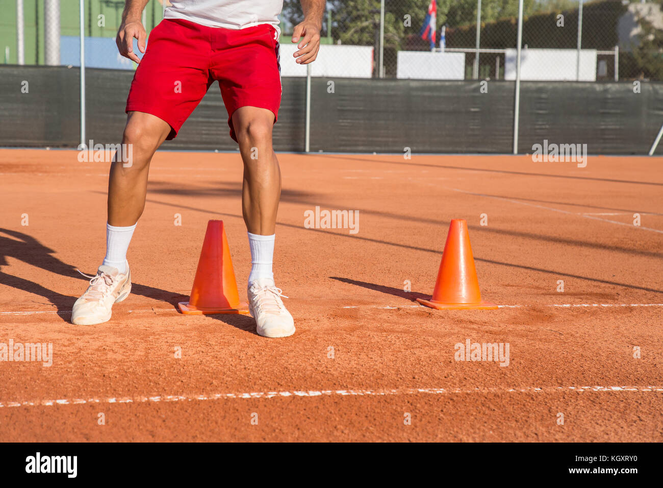 Professional tennis player warming up by dodging cones in zigzag manner. - Stock Image