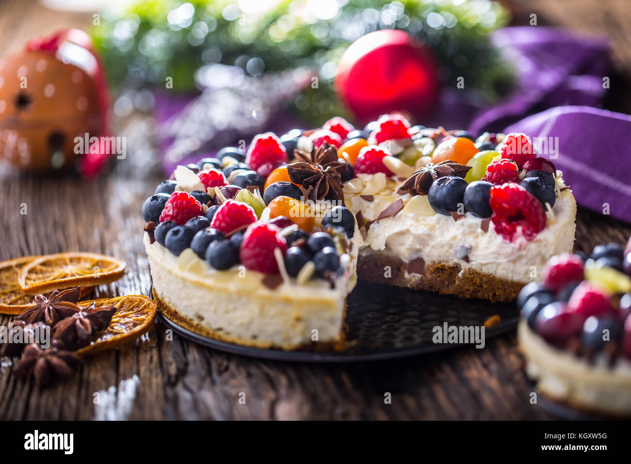 Cheescake with fresh fruit berries strawberries raspberries and star anise. Christmas cheescake with christmas decoration. - Stock Image