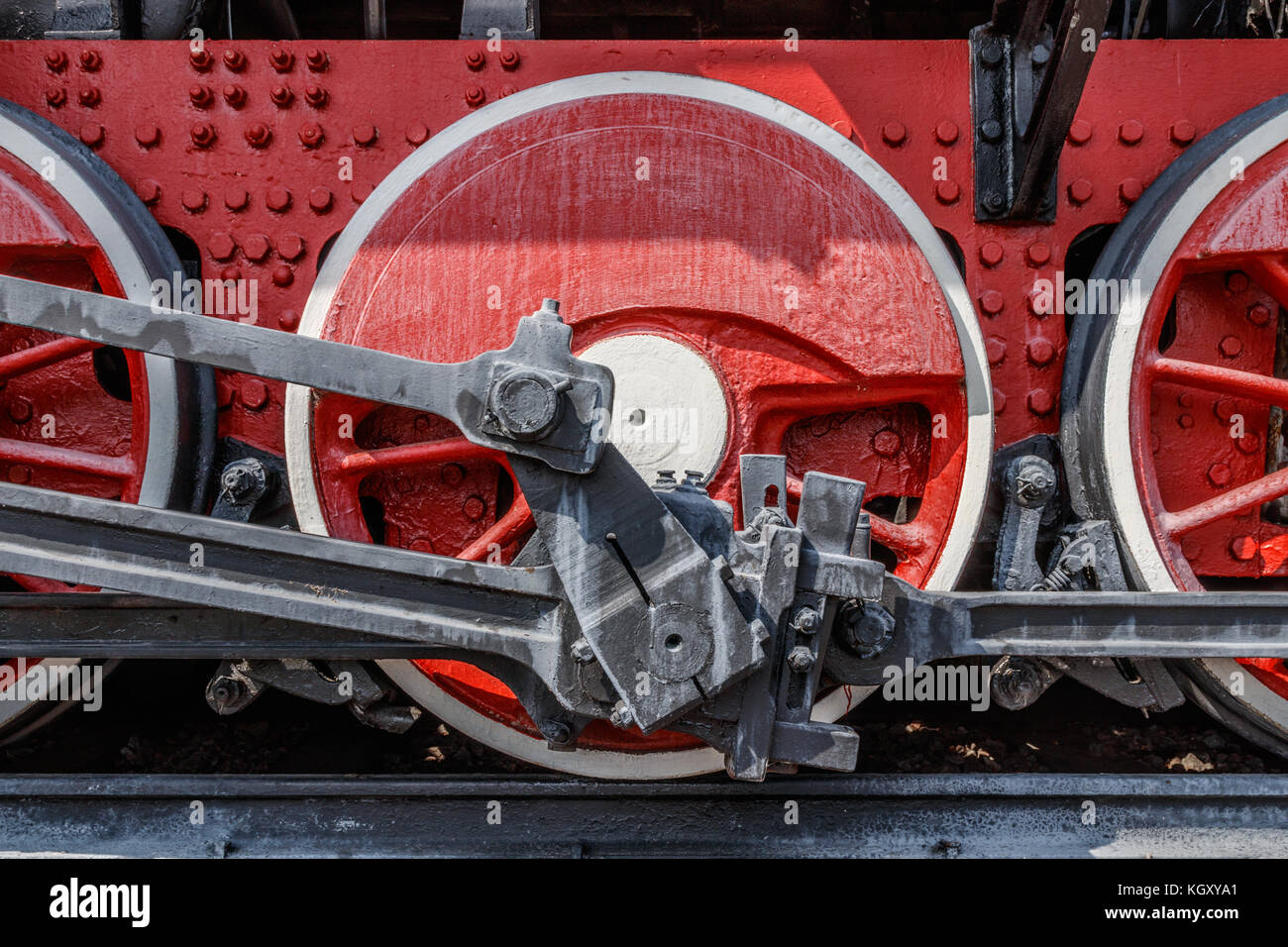 Red frame and wheels of a steam locomotive with cranks, rods and axles. Stock Photo