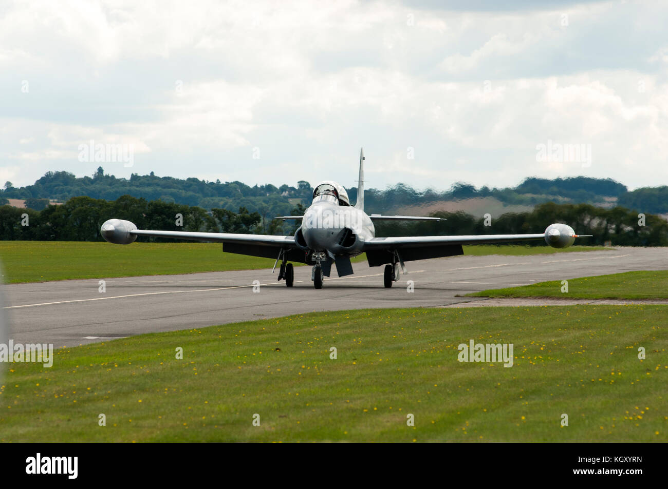 An American 'Coldwar' jet fighter is shown taxiing along a runway on an airfield. - Stock Image
