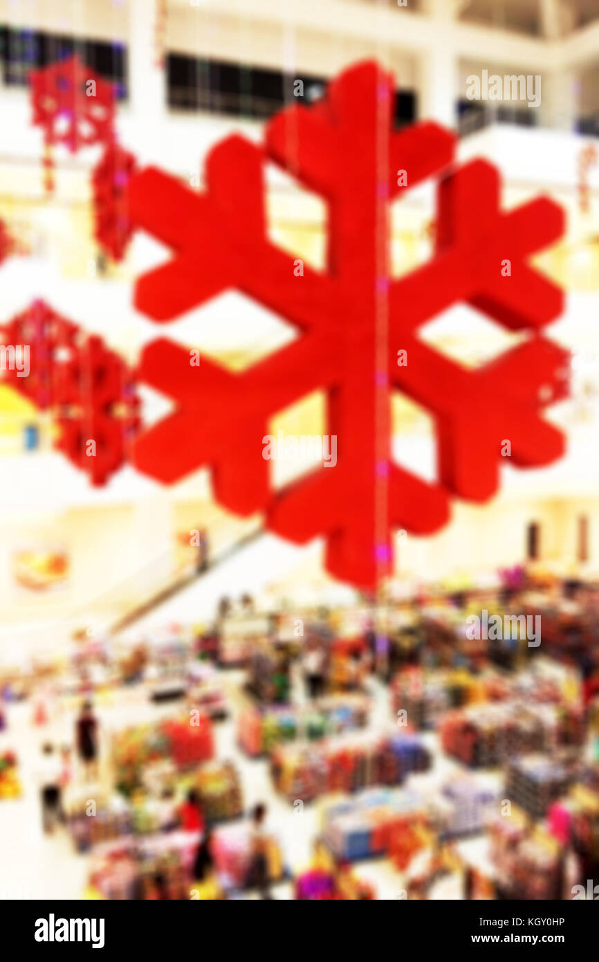 Colorful blurred background of Christmas decoration over a crowded shopping center - Stock Image