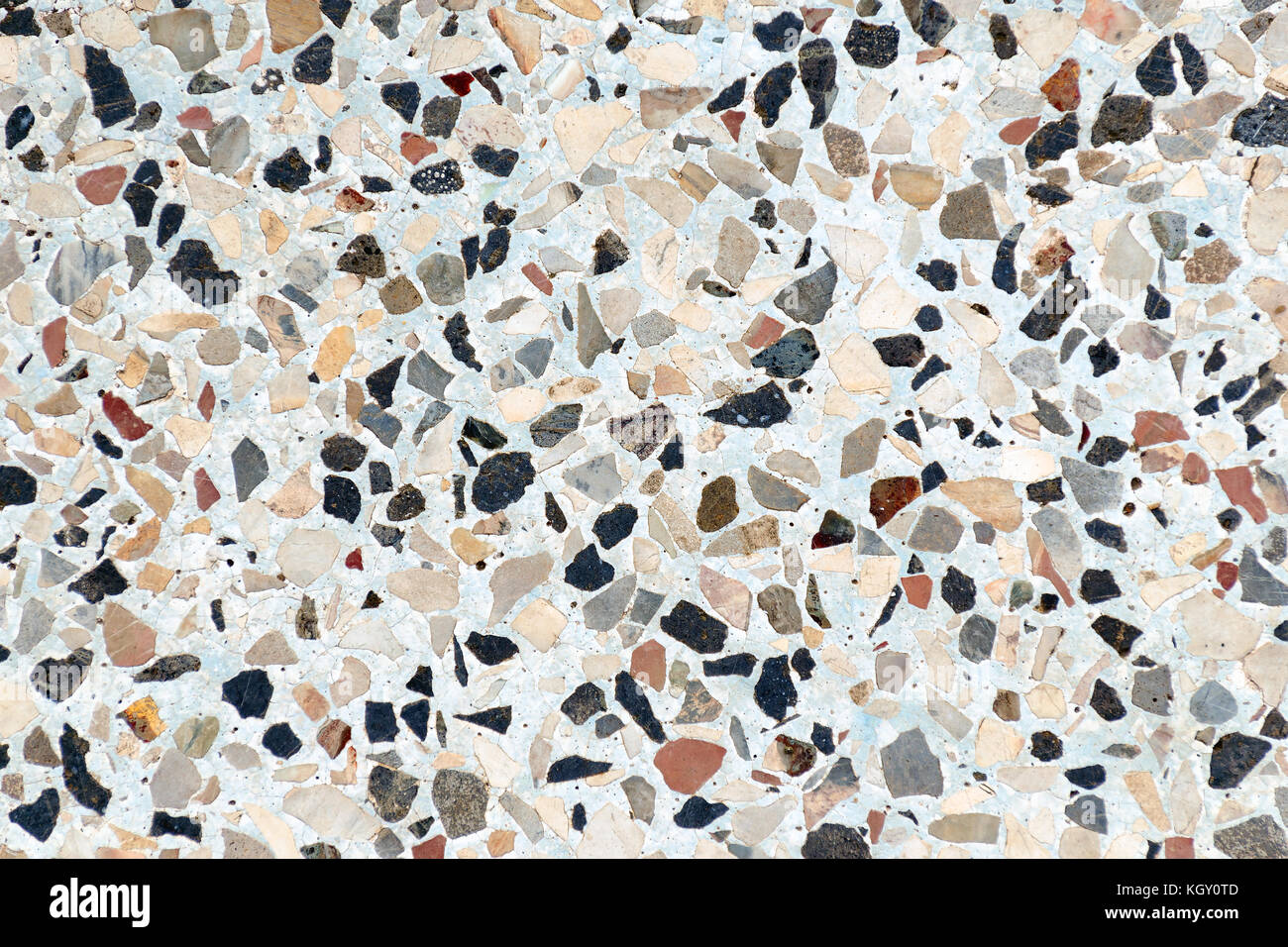 Multi-colored small flat stones are immersed in concrete. Abstract background. - Stock Image