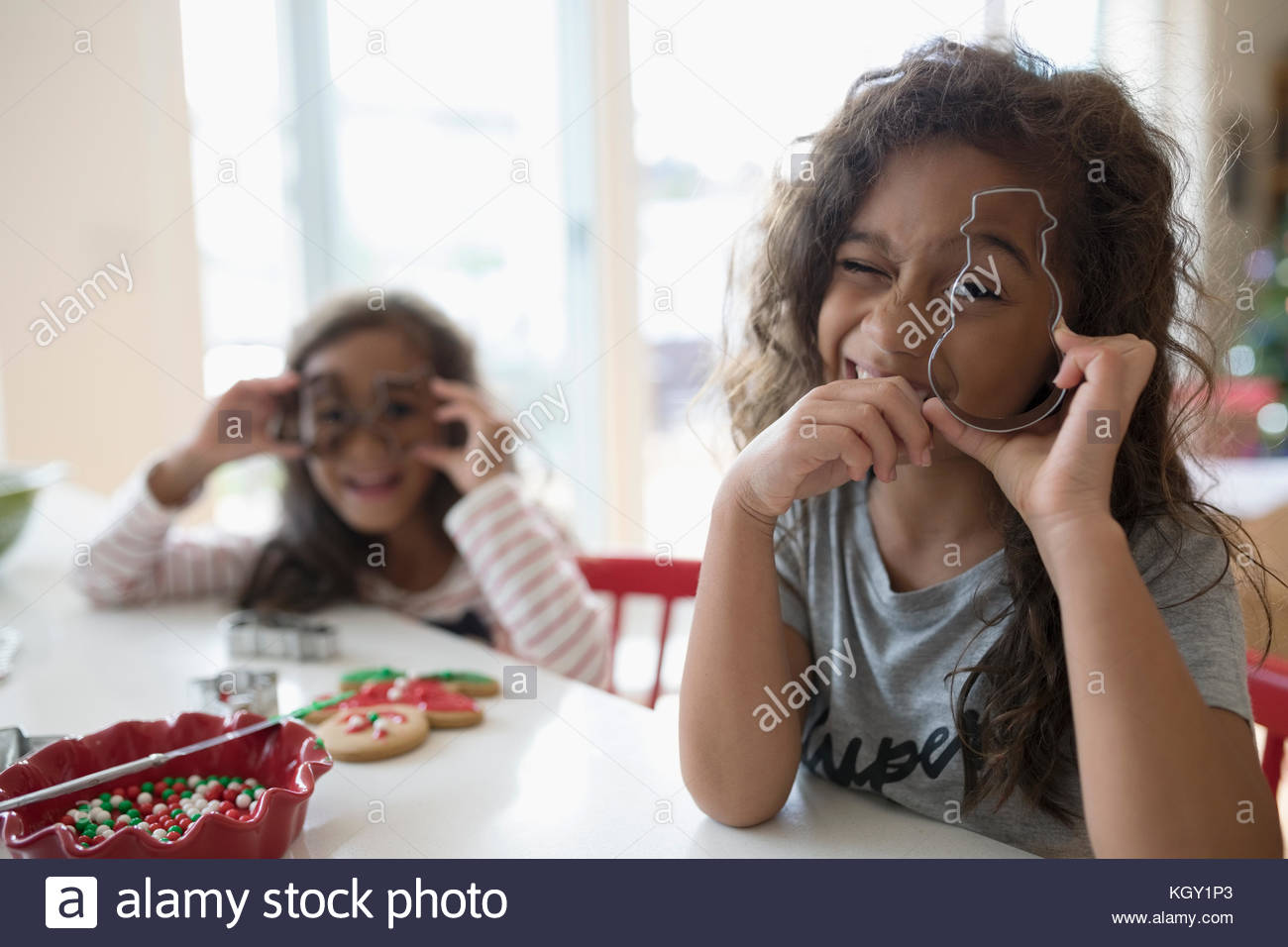 Portrait playful girl sisters with Christmas cookie cutters baking in kitchen - Stock Image