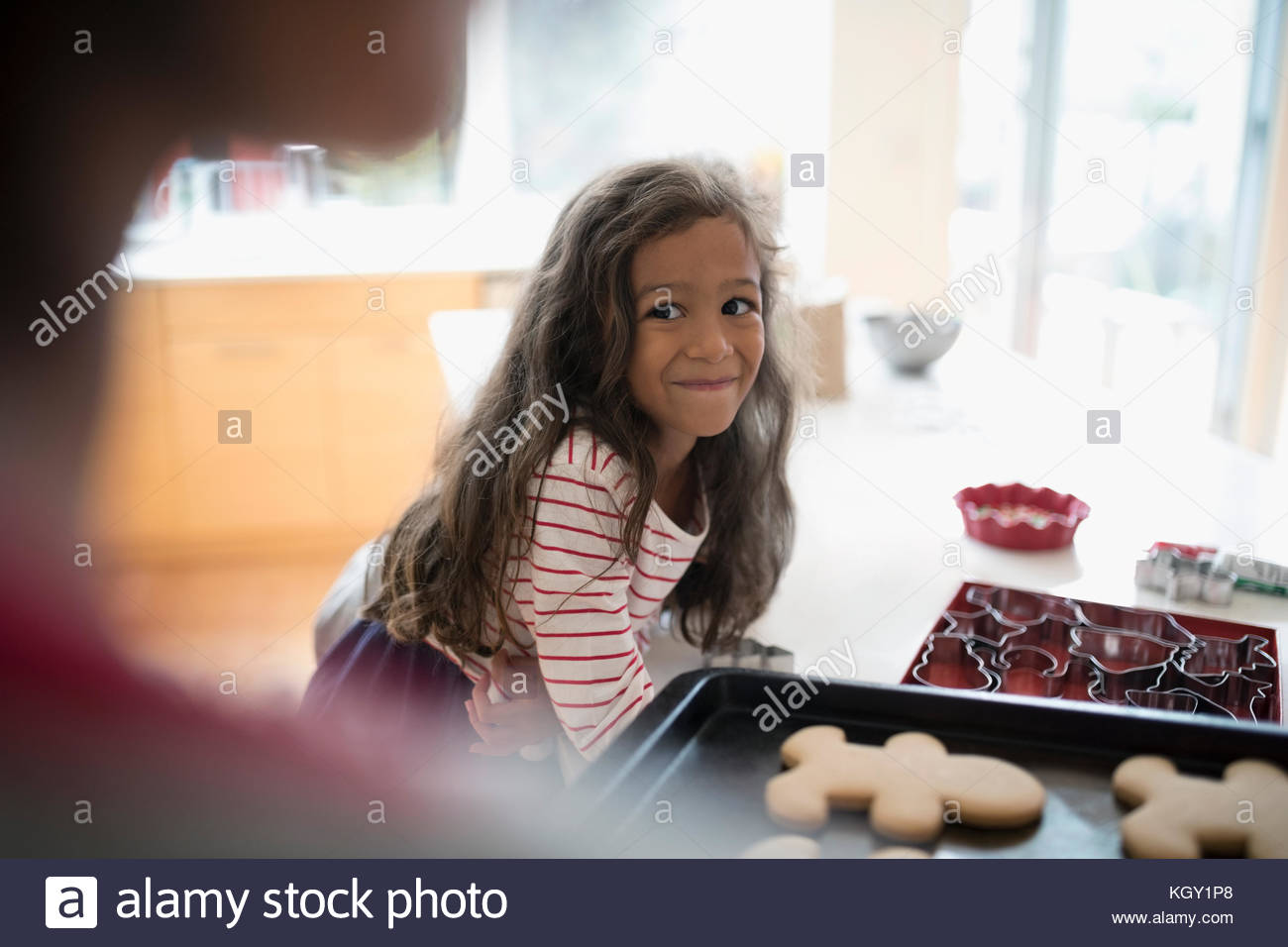 Excited daughter watching mother with fresh, hot Christmas gingerbread cookies - Stock Image