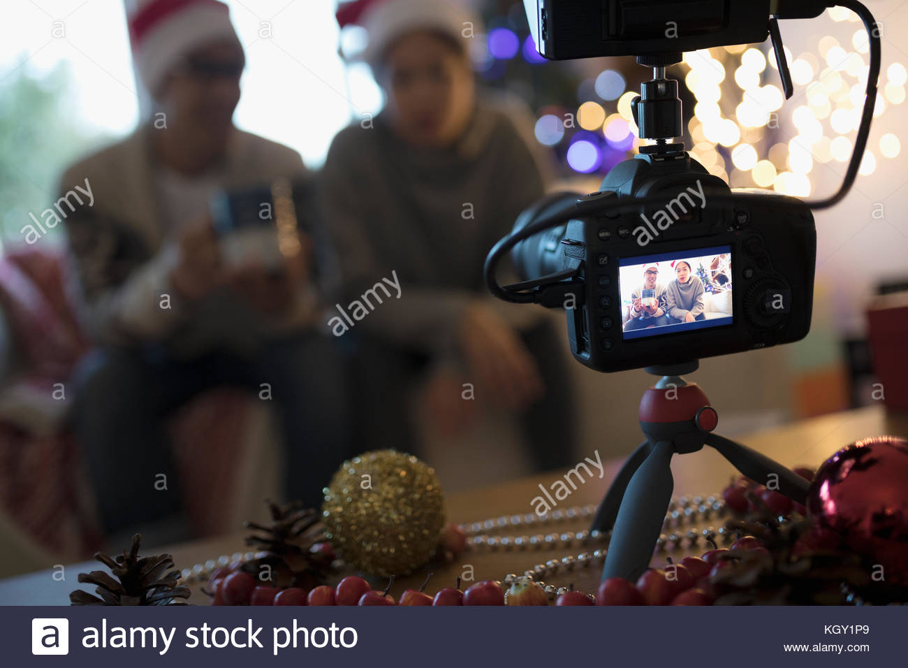 View through camera viewfinder of couple wearing Santa hats in Christmas living room - Stock Image