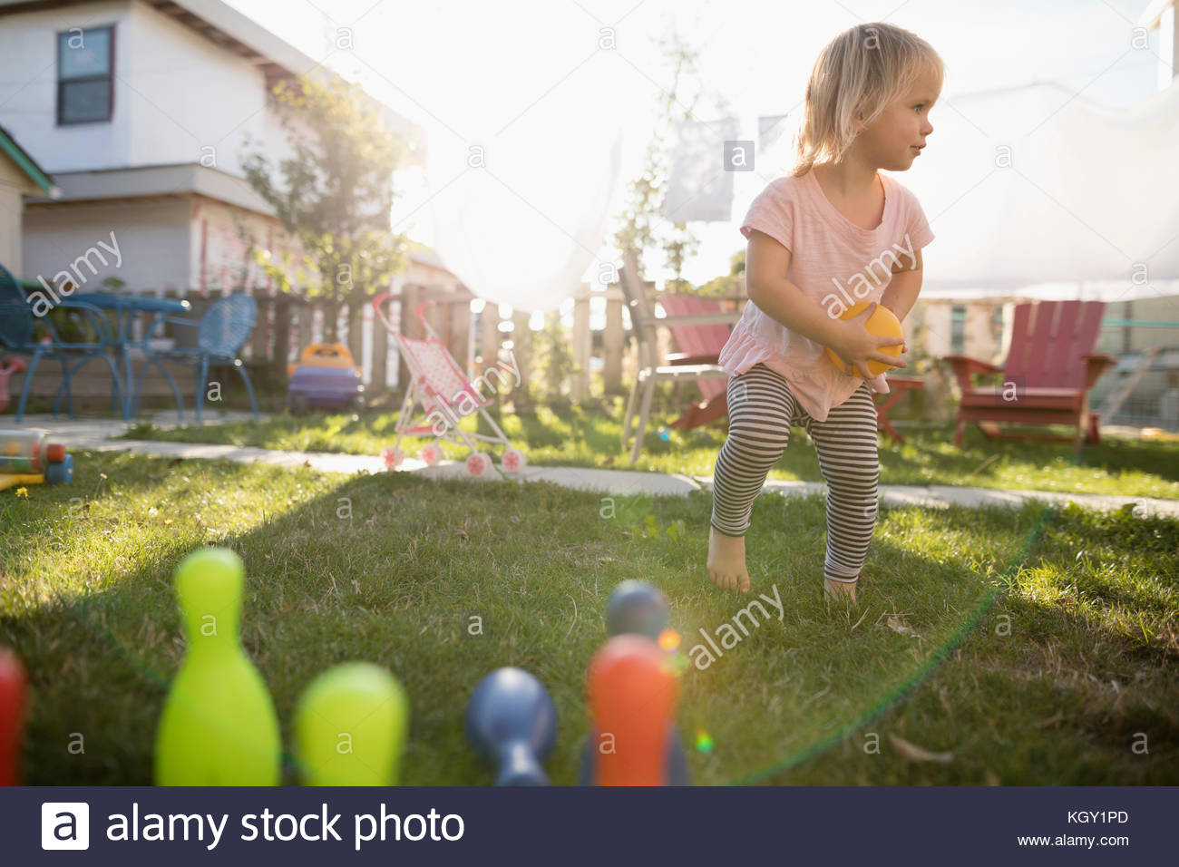 Cute toddler girl playing with bowling toy in grass in sunny backyard - Stock Image