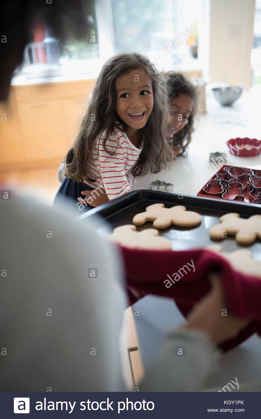Excited daughters watching mother with fresh, hot Christmas gingerbread cookies - Stock Image