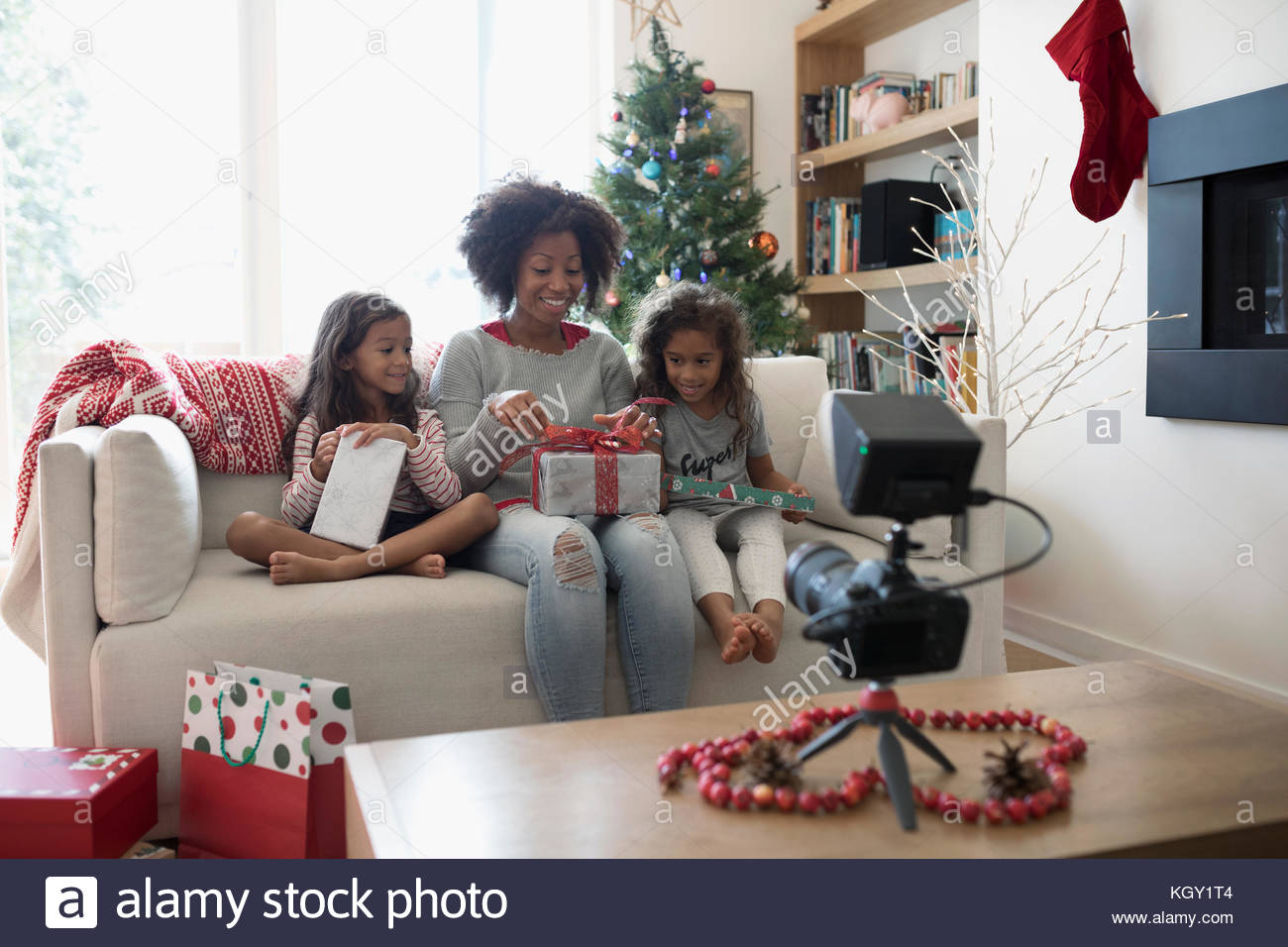 Mother and daughters opening Christmas gifts for video camera in living room - Stock Image