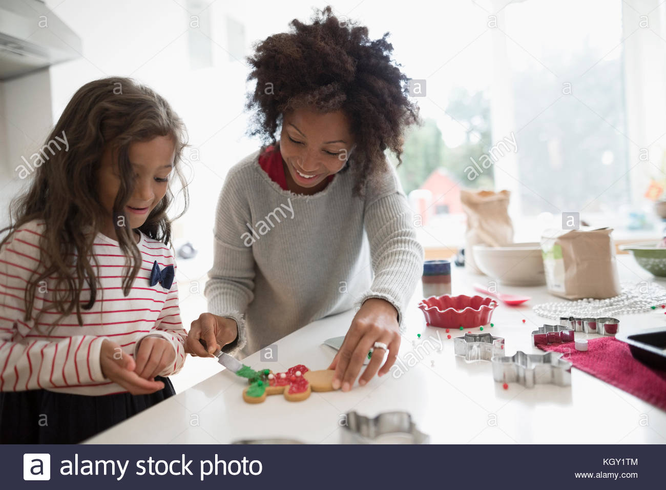 Mother and daughter decorating Christmas gingerbread cookies in kitchen - Stock Image